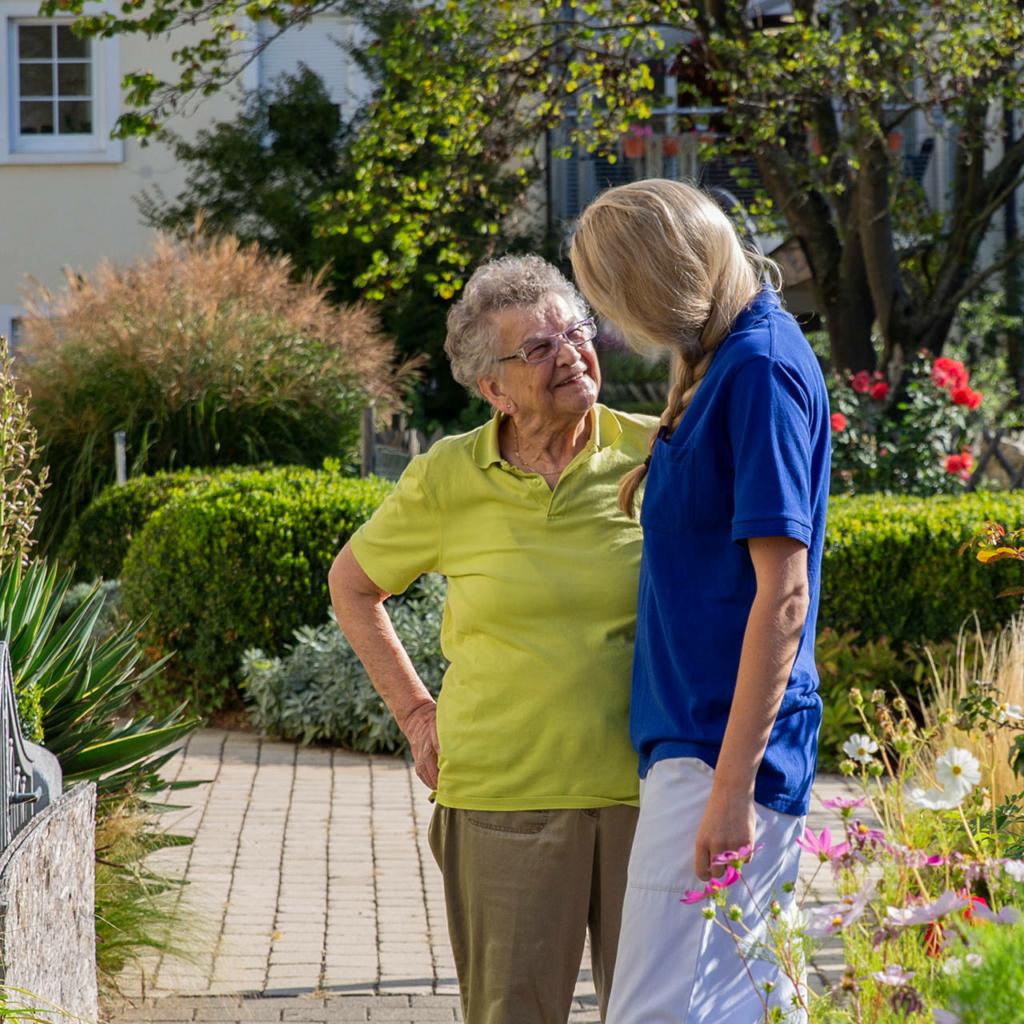 Ältere Frau und Mitarbeiterin unterhalten sich draußen im Grünen